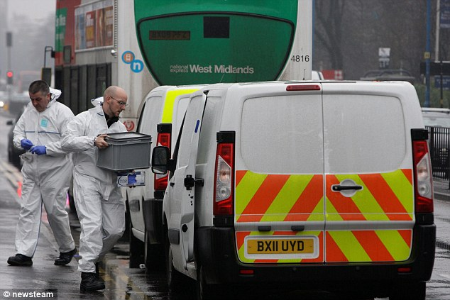 Probe: Forensics experts load evidence into a van as a manhunt got underway to find the killer