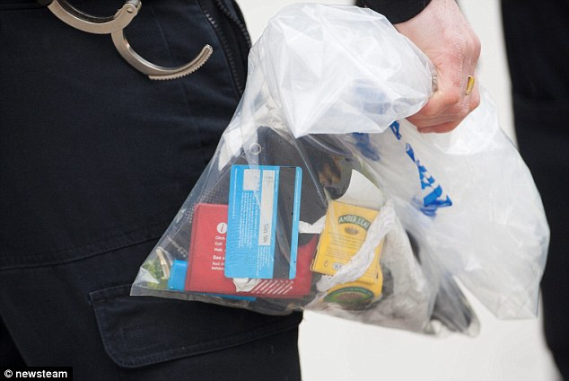 Clues: A police officer carries an evidence containing a bank card, bus pass and rolling tobacco