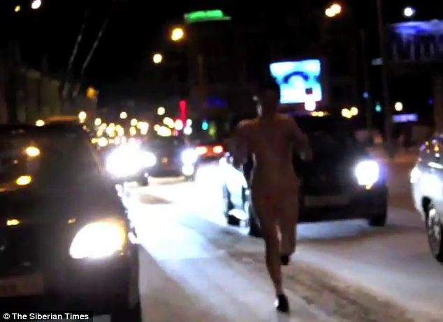 A runner was filmed running along a busy motorway in Tomsk, Siberia, wearing only a bikini and trainers