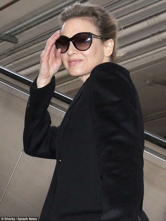 In the shade: Renee kept her large glasses on as she rode the escalator out of LAX