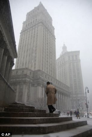 A man climbs courthouse steps in lower Manhattan during a storm on Friday