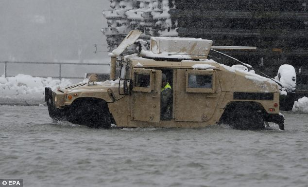 Look out: United States National Guard soldiers drive through deep water in Scituate, Massachusetts