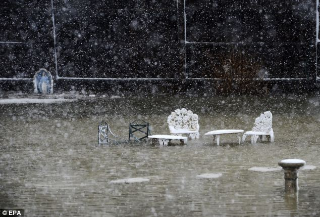 Ravaged: Yard furniture sits in a flooded yard in Scituate, Massachusetts after coastal flooding