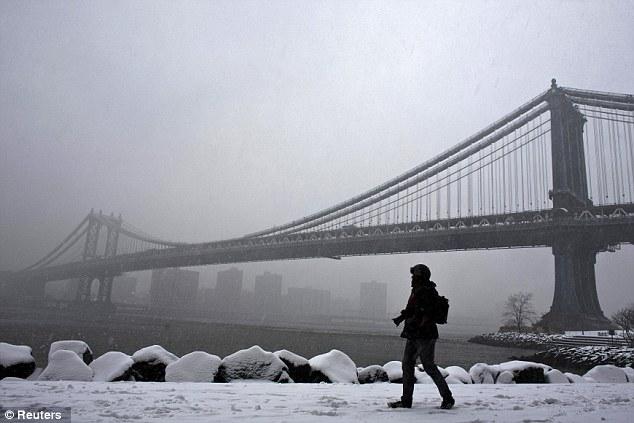 Snowstorm: A man walks through Brooklyn Bridge Park on Friday as as many as 6 inches of snow fell