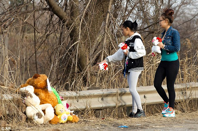 Dominique Ellison, left, and Rickie Bowling, of Warren, bring stuffed animals to a memorial in honor of their friends who died in the car crash
