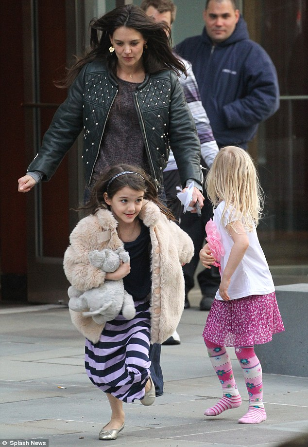 Making a run for it: Suri Cruise dashed away from her mum Katie Holmes as the pair left a New York City apartment building on Sunday