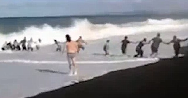 Human chain: Video of the rescue shows the group holding hands as they drag Joshua from the strong surf