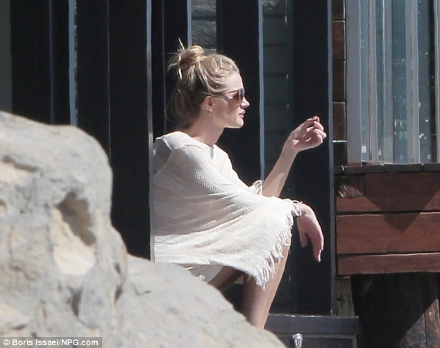 Soaking up the sun: The stunning star later sported a loose fringed cream shawl as she sat on the beach to take in the spectacular view