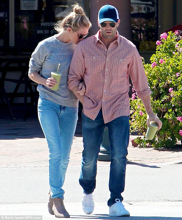 Casual class: Rosie still looked stunning in a low key outfit of loose grey sweater, blue jeans and beige boots as she dropped a kiss on her beau's shoulder