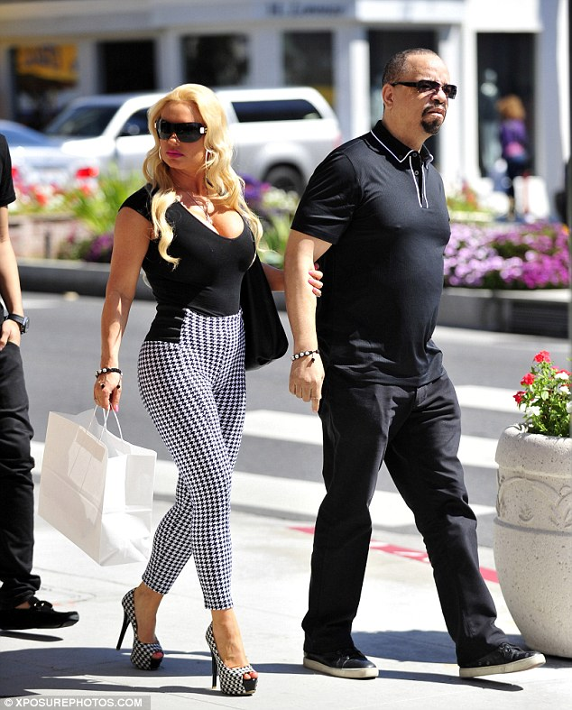 Tottering along: Coco held Ice-T's arm as they strolled down Sunset Boulevard - and she needed the extra support in those high heels