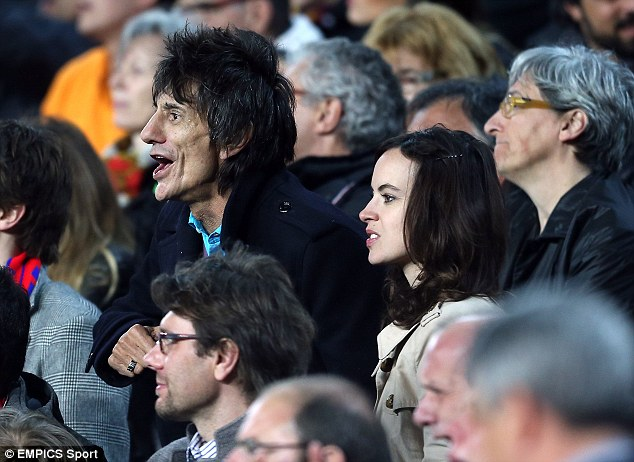 Excited: Ronnie Wood enjoying the action with his wife Sally... and with a cigarette (below)