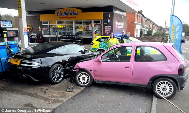Expensive mistake: Onlookers watched in horror as the little pink runabout crashed into the £100,000 Aston Martin in Swindon yesterday. Corsa driver Natasha Gregory says she feels like a 'total d*** head' over the accident