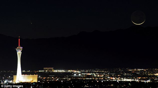 Bright lights: PanSTARRS, the bright dot in the top-right, passes over the Stratosphere Casino Hotel along with a waxing crescent moon over the Spring Mountains range last in Las Vegas, Nevada