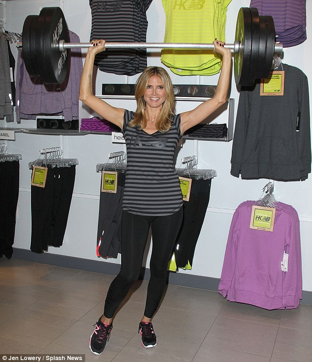 No sweat! Heidi Klum holds a weight prop above her head as she attends a photocall to launch her latest New Balance collection in Culver City, California, on Thursday