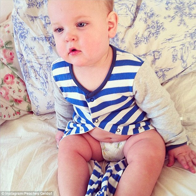 Cutie pie: The little one looked positively adorable in his blue and white striped romper suit