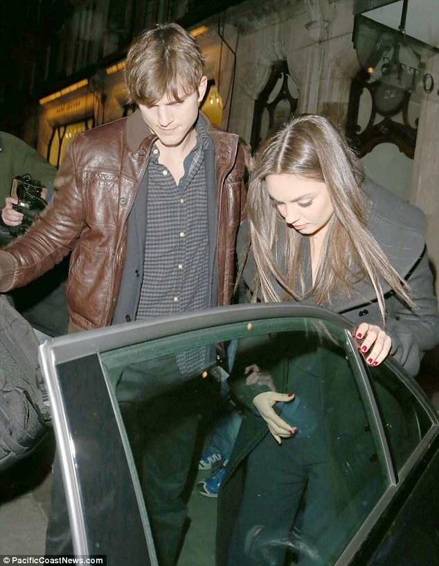 The perfect gent: Ashton makes sure Mila gets into the car safely as they leave Scotts Restaurant in London