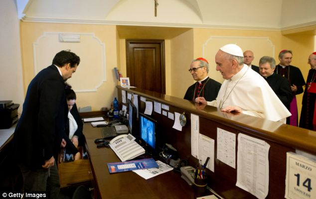 Squaring up: Pope Francis pays his bill at the Casa del Clero residence after being named as the new leader