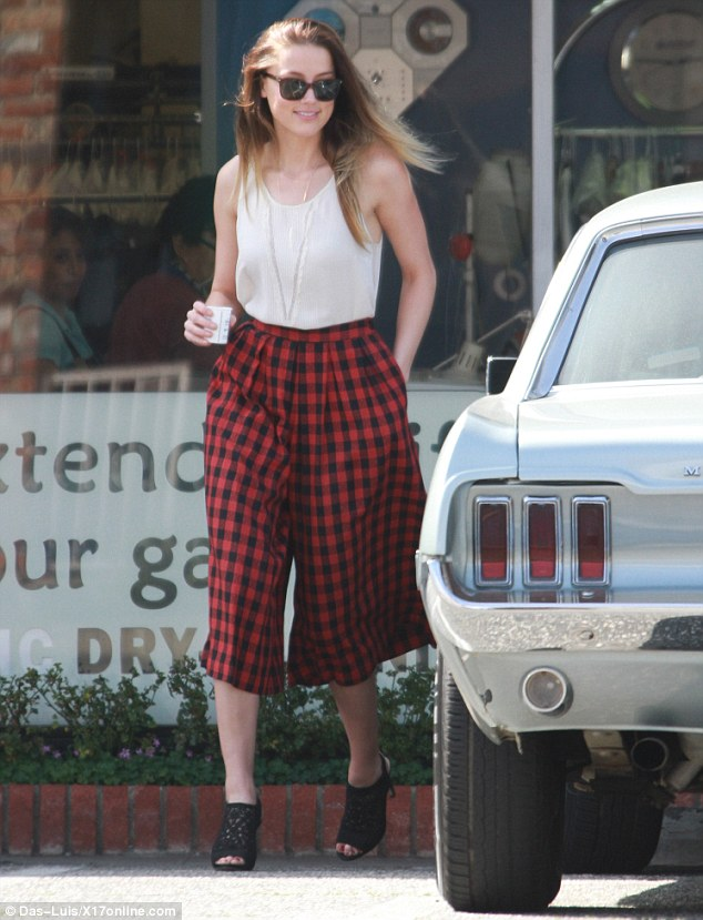 Pulling it off: The 26-year-old teamed her flowing cropped trousers with a slinky blouse and open toe heels