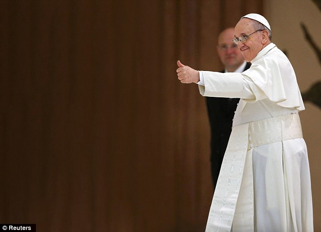Rise to the top: Pope Francis gives journalists a thumbs-up at the Vatican yesterday