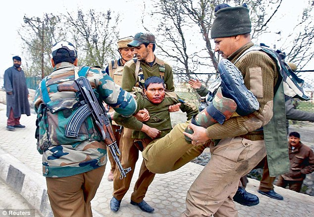 Paramilitary soldiers carry their injured colleague to a hospital during a gunfight in Srinagar on March 13
