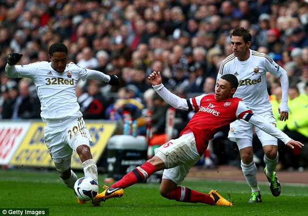 Battle: Jonathan de Guzman is tackled by Alex Oxlade-Chamberlain in Saturday's match at the Liberty Stadium