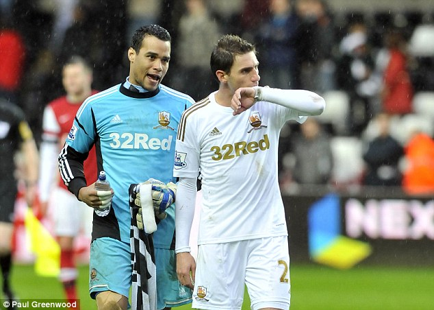 Disappointment: Michel Vorm (left) and Angel Rangel start the post-mortem after the defeat to Arsenal