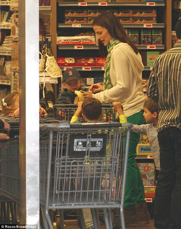 Her lil' monkey: Garner gave tiny Samuel a bite of banana as he sat in the grocery cart surrounded by children