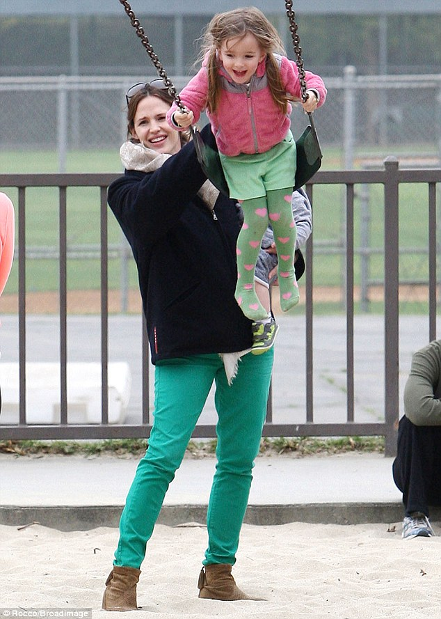 Spreading the fun around: Showing she's an active mum, Garner also pushed one of her daughters on the swing during the family day out