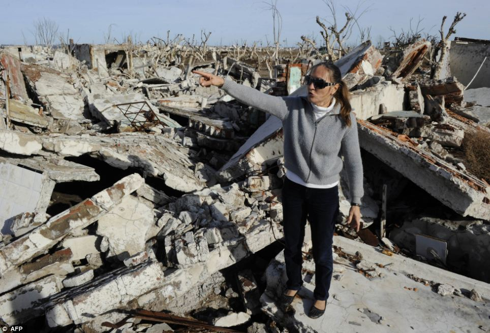 Childhood home: Norma Berg, 48, next to the ruins of her family house. She said a few days before the flood her pets ran away - she believes they could sense the incoming water