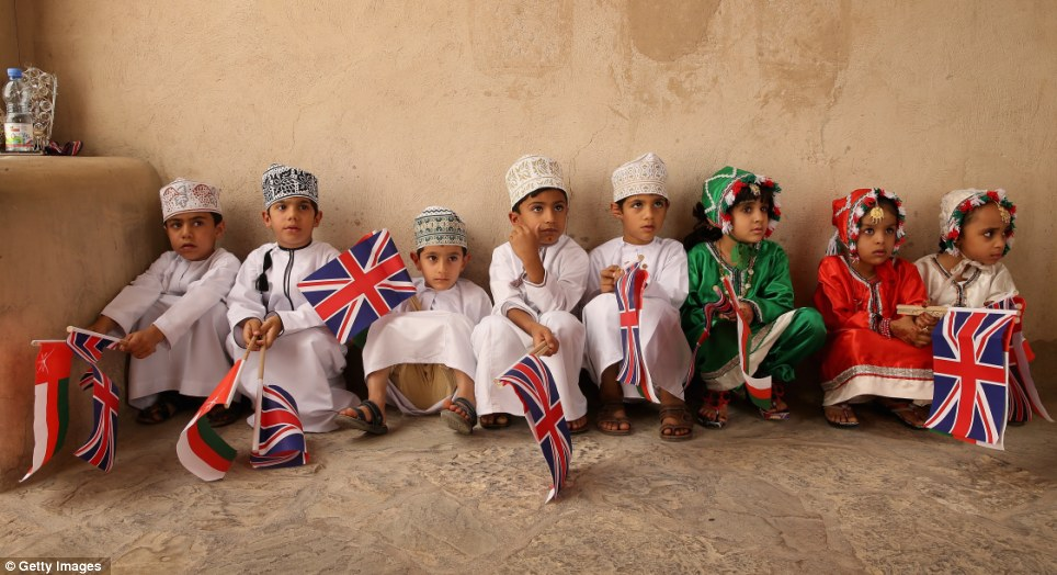 Waiting for a prince; Young Omani children in traditional dress wait in the shade before greeting Prince Charles, Prince of Wales and Camilla, Duchess of Cornwall