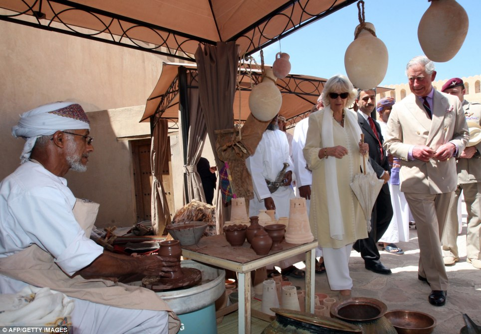 Souveniring in Oman: Charles and Camilla stop by a stall where a local Omani man is making claypots and models of the fort's towers