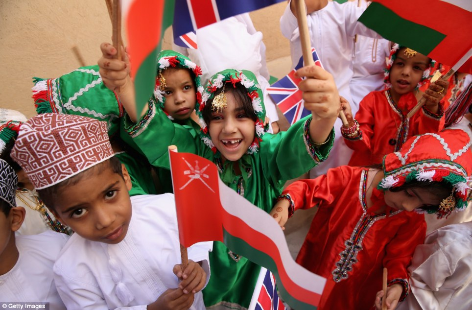Welcoming smiles: Young children wearing traditional dresses and caps, wave flags to welcome Charles and Camilla to Nizwa