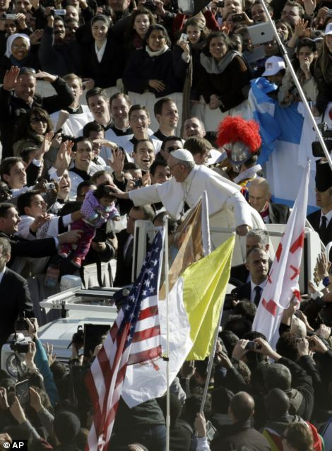 Pope Francis pats a baby as he is driven through the crowd prior to his inaugural Mass