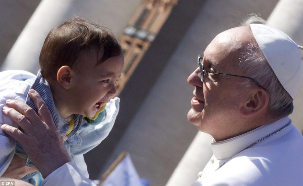 Holy meeting: Although the new leader of the Catholic Church smiled widely as he picked up a child offered to him, the baby was not quite so cheerful