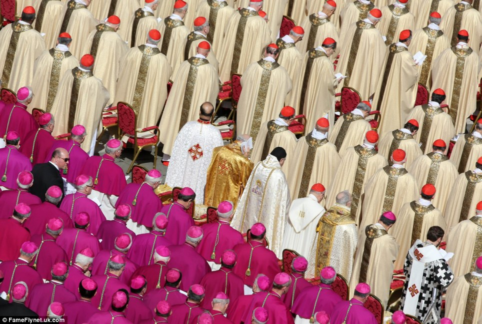 Bishops in pink and cardinals in gold bow their heads in prayer during the open air mass in St. Peter's Square