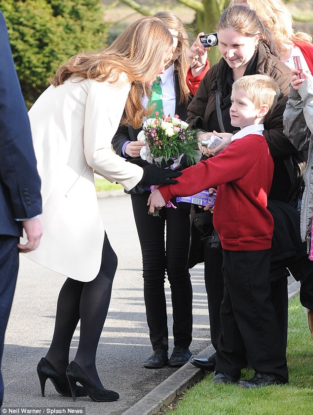 Kate receives a bouquet of flowers from a young admirer outside