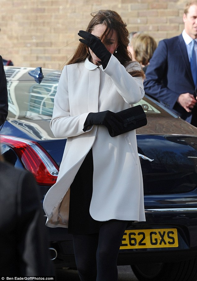 Kate battles the wind to make her way towards the crowds to accept their congratulations and flowers