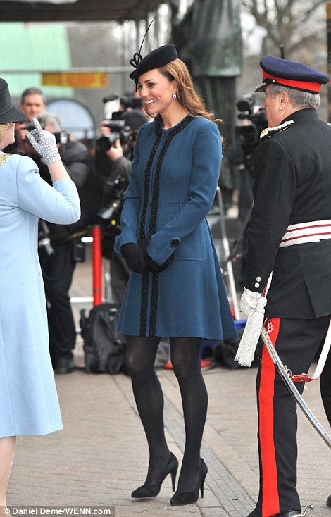 She wears it well: Kate paired a rather short teal coat by Marlene Birger with a jaunty black hat, thick black tights and four inch heels