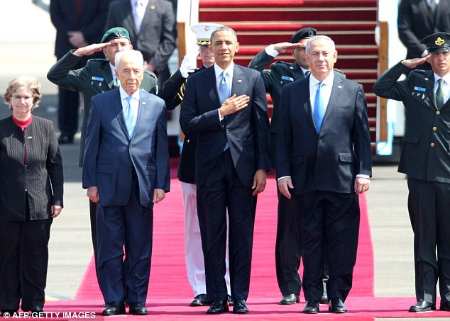Respectful: The three leaders listen to the national anthem shortly after Obama touched down in Tel Aviv