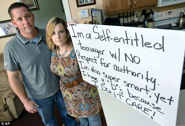 Gentry and Renee Nickell show the sign which they forced their 13-year-old daughter to hold at the side of a busy intersection in Florida on Saturday
