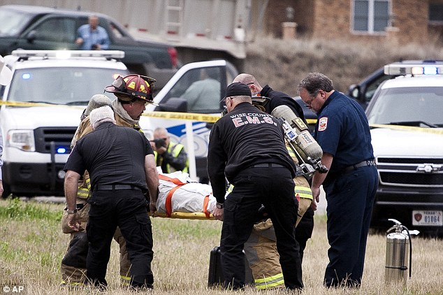 'Basically dead': Emergency personnel carry the suspect away on a stretcher after he was shot in the head following a 100mph police chase