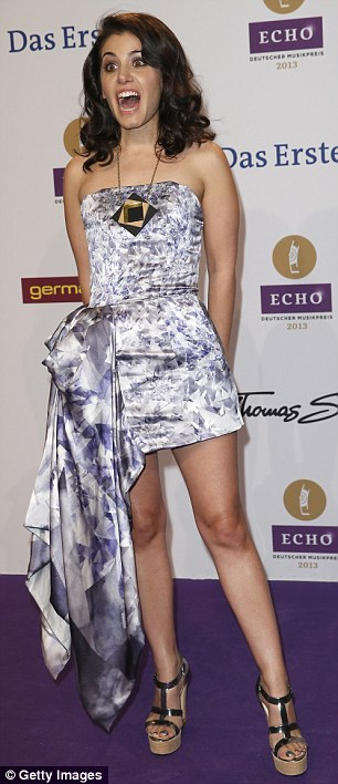 Bizarre: Katie pulls faces on the purple carpet as she poses solo