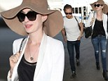Classic beauty: Anne Hathaway was the picture of 1950s glamour as she headed to departing flight with husband Adam Schulman