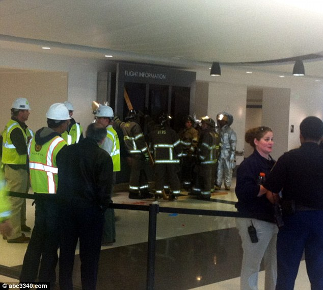 First responders: The massive flight information board is seen propped up against the wall among rescue workers just after the horrific accident