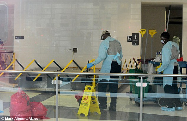 Closed off: Two workers are seen cleaning in a closed off section of the terminal where the large sign, said to be between 300-400 pounds, fell off the wall