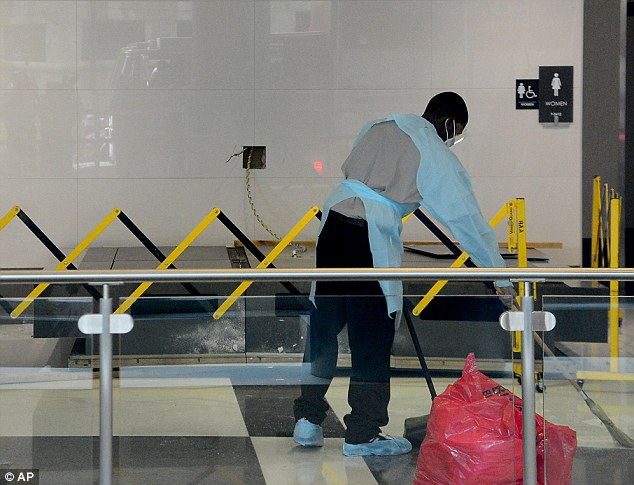 Safety measures: Barricades have since been placed around the airport's other flight status boards, the fallen one seen behind a worker here, as a precautionary measure