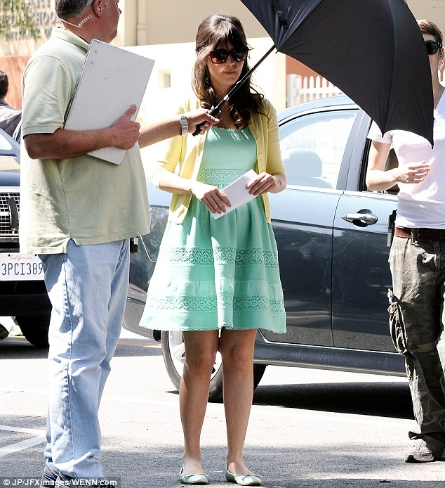 Shady lady: Zooey took a break from the sun in between takes, with an assistant holding an umbrella to shade her face from the California sunshine