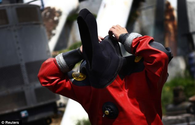 Julio Cu Camara suits up for a dive in Mexico City's sewage system to clear blockages and make repairs