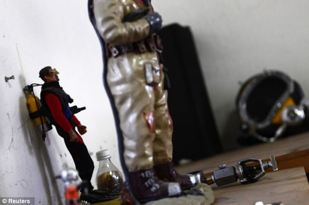 Figurines of divers stand inside Julio Cu Camara's office at the drainage system plant in Mexico City