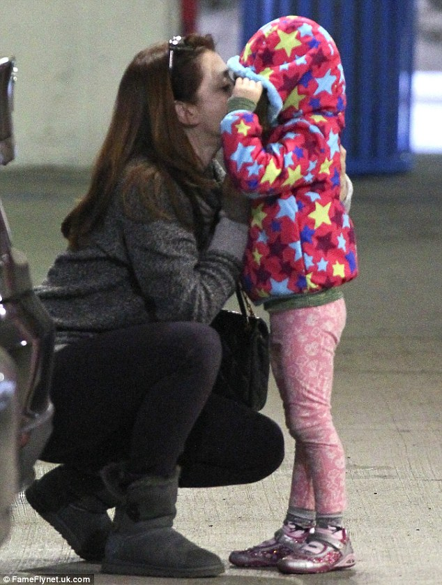 Give mommy a kiss: The redheaded funnywoman, who's turning 39, affectionately squatted down to kiss her toddler